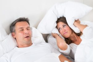 woman covering ears while man snore